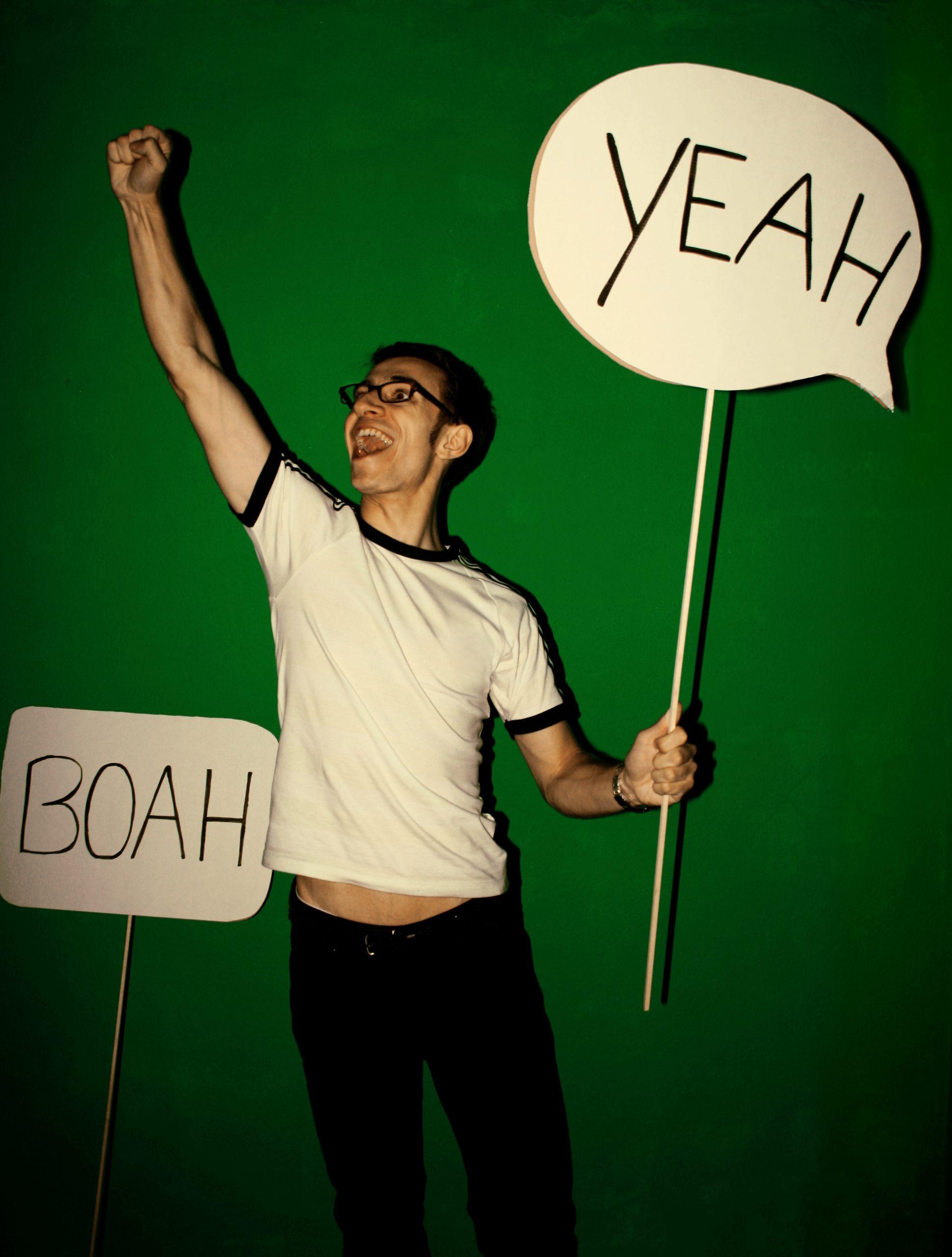 """Ein begeisterter Mensch äußert sich mit gezeichneten Sprechblasen an Stöckern mit """"Yeah"""" und """"Boah""""."""
